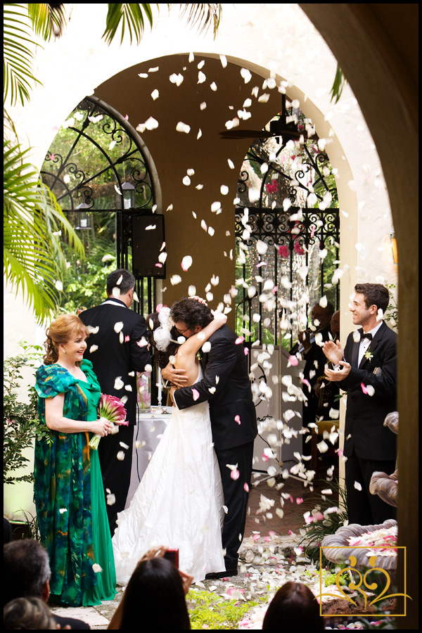 Rose petals float down onto the happy couple as they have their first kiss.